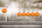 Newtons cradle above city — Stock Photo