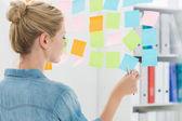 Vista traseira de uma artista feminina a olhar colorido sticky notes — Fotografia Stock