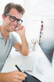 Vista lateral de un editor de foto casual male usando tableta gráfica — Foto de Stock