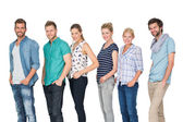 Casual happy people standing with hands in pockets — Stock Photo