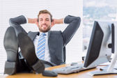 Relaxed businessman sitting with legs on desk — Stock Photo