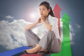 Composite image of businesswoman sitting cross legged with hands — Stock Photo