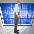 Composite image of happy businessman standing with hands in pock — Stock Photo