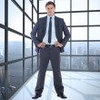 Composite image of serious businessman with hands on hips — Stock Photo