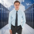 Stock Photo: Composite image of serious businessmwith hand in pocket