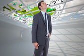 Composite image of serious businessman with hand on hip — Stock Photo