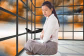 Composite image of businesswoman sitting cross legged with arms — Stock Photo