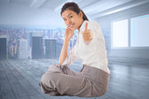 Composite image of businesswoman sitting cross legged showing th — Stock Photo