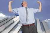 Composite image of businessman standing with hands up — Photo