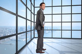 Composite image of smiling businessman with hand on hip — Stock Photo