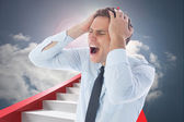 Composite image of stressed businessman with hands on head — Stock Photo