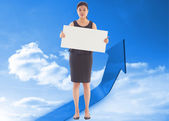 Composite image of businesswoman holding a placard — Стоковое фото