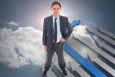 Composite image of stern businessman standing with hand on hip — Stock Photo