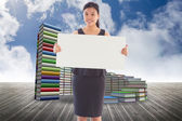 Composite image of businesswoman holding a placard — Stock Photo