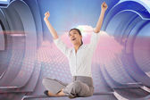 Composite image of businesswoman sitting cross legged cheering — Stock Photo