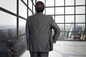 Composite image of businessman with hand on hip — Stock Photo