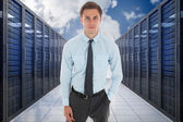 Composite image of serious businessman with hand in pocket — Stock Photo