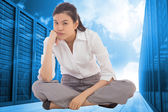 Composite image of grumpy businesswoman sitting cross legged — Stock Photo
