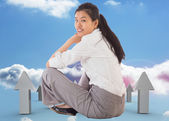Composite image of businesswoman sitting cross legged smiling — Stock Photo