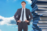 Composite image of smiling businessman with hands on hips — Stock Photo