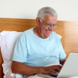 Senior man sitting in bed using laptop — Stockvideo