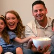 Happy family watching television eating popcorn — Stock Video #42644997