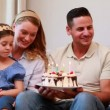 Young family sitting on sofa celebrating a birthday — Stock Video #42647011