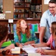 Students revising together in the library with their tutor — Stockvideo