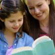 Mother and daughter reading together on a park bench — Stock Video