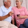 Senior couple sitting on floor drinking red wine — Stock Video