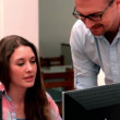 Lecturer explaining something to student in computer class — Vídeo de stock
