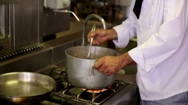 Handsome chef stirring a large pot — Stock Video