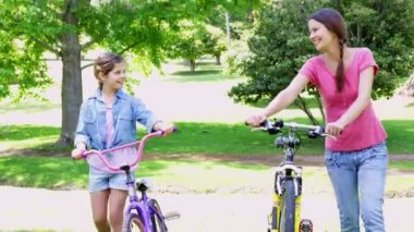 Mother and daughter pushing their bikes together — Stock Video
