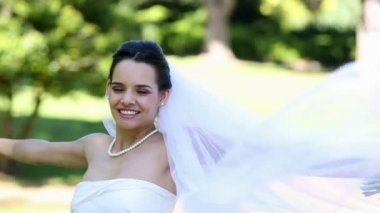 Beautiful bride smiling at camera in the park — Stock Video