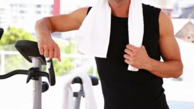 Fit man leaning on exercise bike — Stock Video