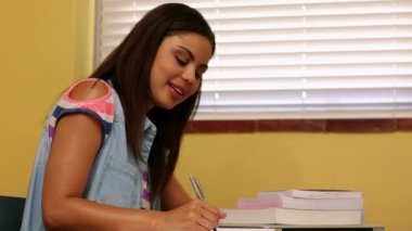 Pretty student studying at desk in classroom — Stock video