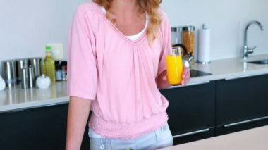 Pretty woman standing with glass of orange juice — Stock Video