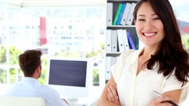 Woman smiling while colleague works behind her — 图库视频影像