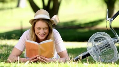 Pretty girl reading beside her bike in the park — Stock Video