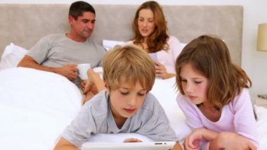 ベッドの中でタブレットを使用しての背後にあるチャットの両親と子供たち — ストックビデオ