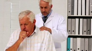 Doctor examining his senior patient who has a cough — Stock Video