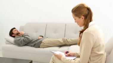 Konuşma terapisti için kanepede yatan genç adam — Stok video