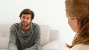 Man sitting on sofa talking to his therapist — Stock Video