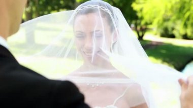 Groom lifting veil off beaming brides face — Stock Video