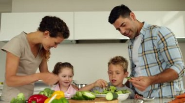 Parents preparing a salad with their children — Stockvideo