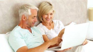 Par chatta och använda laptop i sängen — Stockvideo