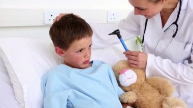 Doctor checking the ears of little sick boy sitting in bed — Stock Video