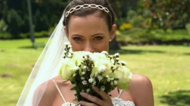 Bride smelling her bouquet in the park — Stock Video