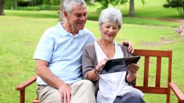 Retired couple sitting on a park bench using a tablet — Stock Video