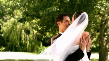 Happy newlywed couple in the park — Stockvideo